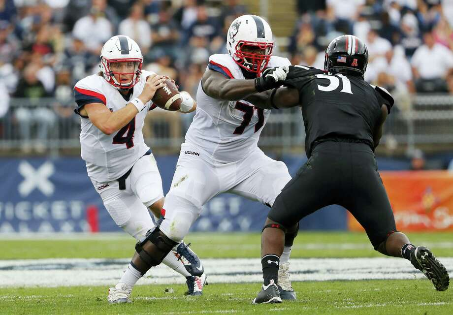 UConn quarterback Bryant Shirreffs runs behind the block of offensive lineman Richard Levy during Saturday's win over Cincinnati. Photo: Winslow Townson — The Associated Press  / FR170221 AP