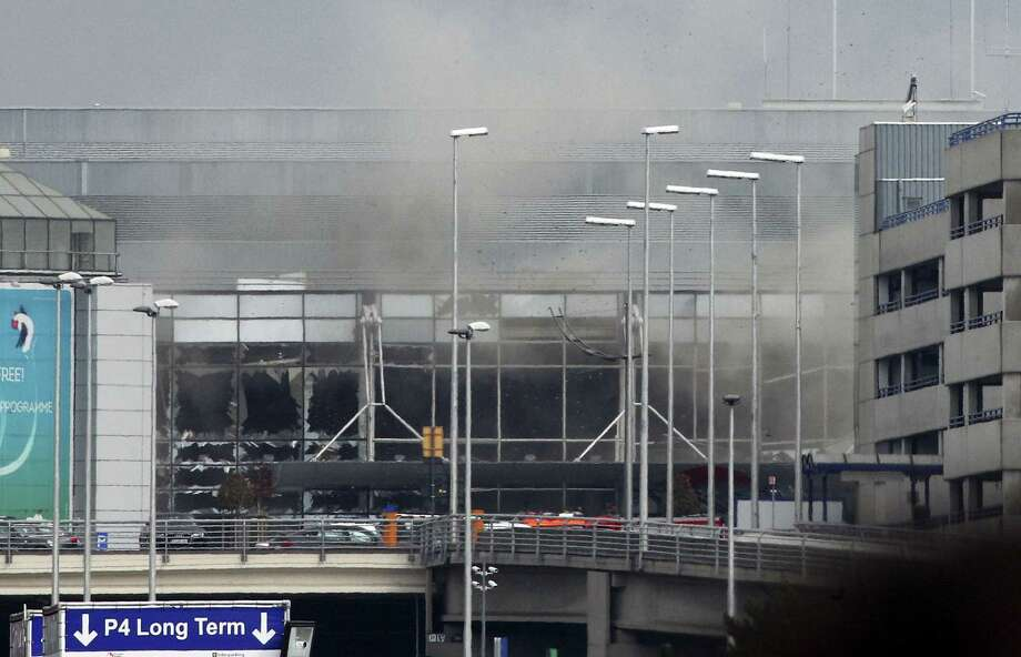 Smoke billows from the  Zaventem Airport after a controlled explosion in Brussels, Tuesday, March 22, 2016. Bombs struck the Brussels airport and one of the city's metro stations Tuesday, killing and wounding dozens of people, as a European capital was again locked down amid heightened security threats. Photo: (AP Photo/Michel Spingler) / AP