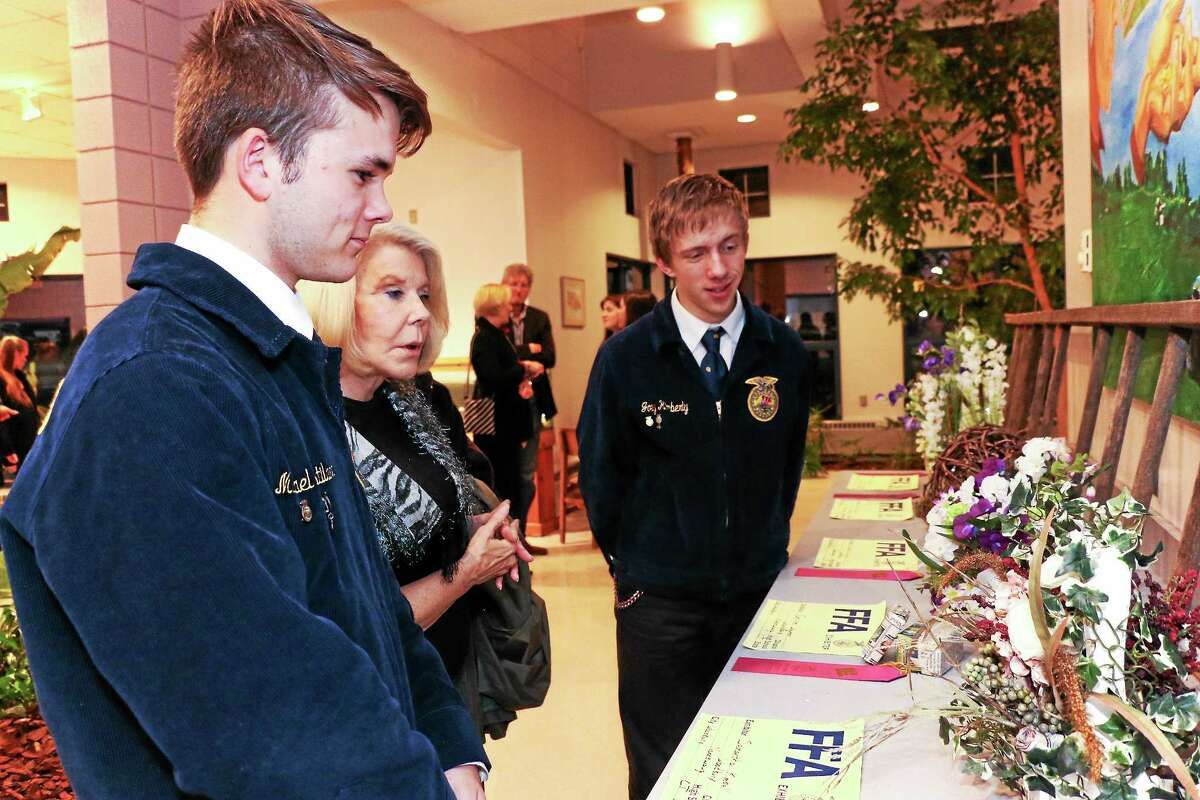 Nonnewaug students Michael Kastilahn, left, and Joe Kimberly of New Milford, tell Sophie Kelley, of Middlebury, about projects developed by some of the students in the Ellis Clark Regional Agriscience and Technology Program at the school.