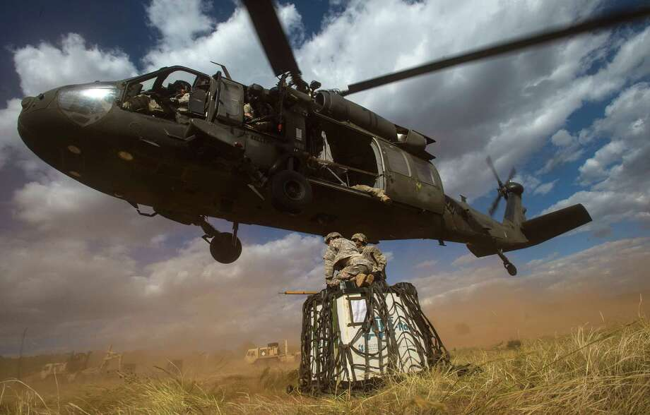 FILE - In this Sept. 23, 2014 file photo, Spc. Melissa Evalle, left, and Spc. Gabriel Torres battle the wind and dirt as a Sikorsky UH-60 Black Hawk flies lower so they can attach a load of supplies to the bird during training down range at Fort Carson in Colorado Springs, Colo. Lockheed Martin on Monday, July 20, 2015 said it is buying Black Hawk helicopter maker Sikorsky Aircraft for $9 billion. Photo: (Christian Murdock/The Gazette Via AP)  / the gazette