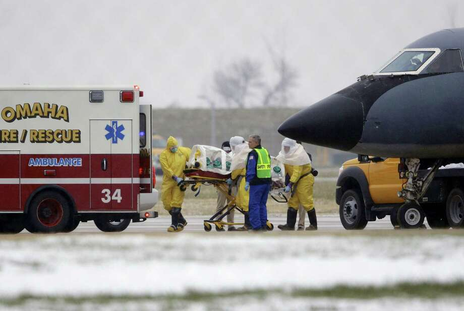 In this Nov. 15, 2014 photo, medical workers in protective suits transport Dr. Martin Salia, a surgeon working in Sierra Leone who had been diagnosed with Ebola, from a jet to a waiting ambulance that will take him to the Nebraska Medical Center in Omaha, Neb. The World Health Organization said on March 12, 2015 that its tally of Ebola deaths has passed 10,000 people, mostly in West Africa. Photo: AP Photo/Nati Harnik, File  / AP