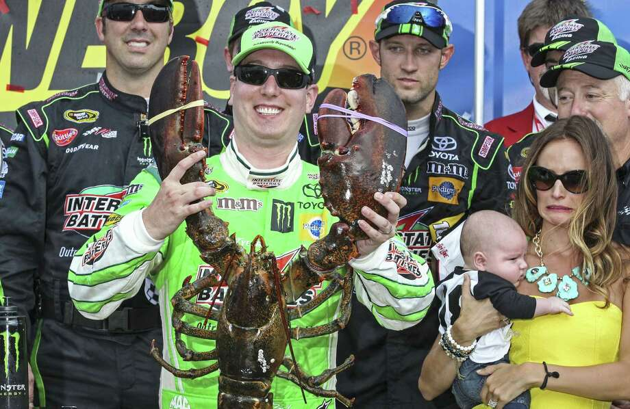 Kyle Busch holds the Loudon lobster trophy in Victory Lane, as his wife, right, Samantha holding son Brexton looks on. Photo: Cheryl Senter — The Associated Press  / FR62846 AP