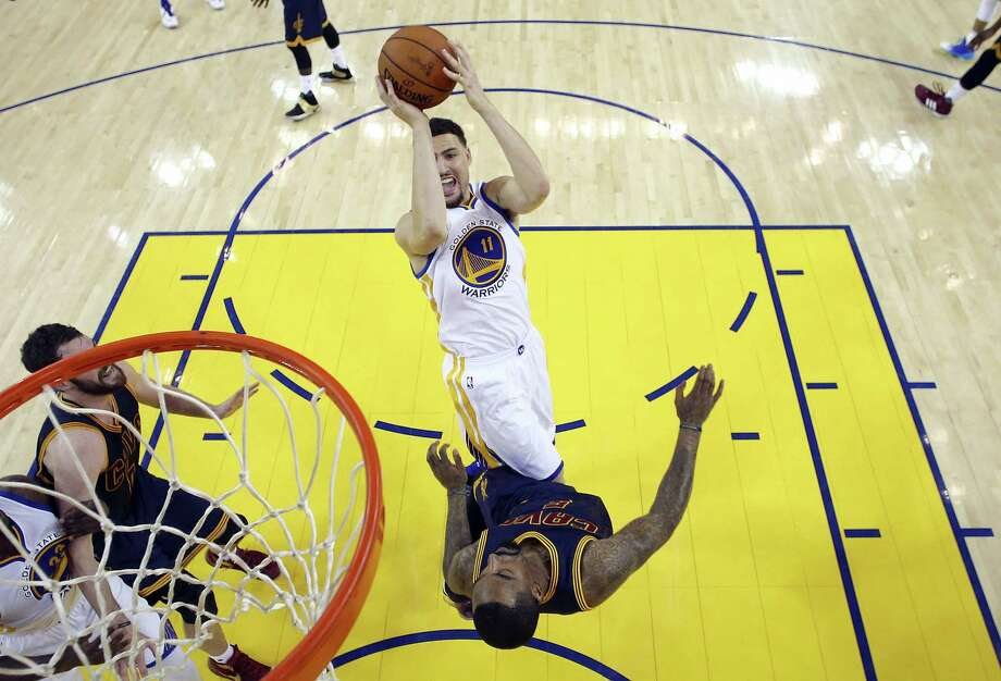 Warriors guard Klay Thompson (11) shoots over Cavaliers guard J.R. Smith during the first half of Game 1 of the NBA Finals on Thursday. Photo: Ezra Shaw — Getty Images Via AP  / Pool Getty Images North America