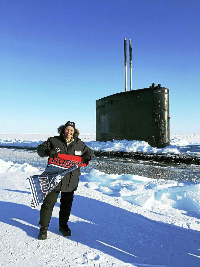 U.S. Sen. Chris Murphy carries a University of Connecticut Huskies banner as he stand outside the USS Hartford,  a Los Angeles-class submarine, after it surfaced in the Arctic. Photo: (Contributed)