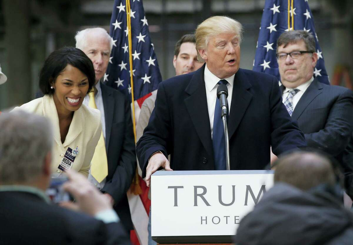 Alicia Watkins of Gaithersburg, Md., left, reacts as she talks to Republican presidential candidate Donald Trump after asking him for a job, while he was speaking during a campaign event in the atrium of the Old Post Office Pavilion, soon to be a Trump International Hotel, Monday in Washington.