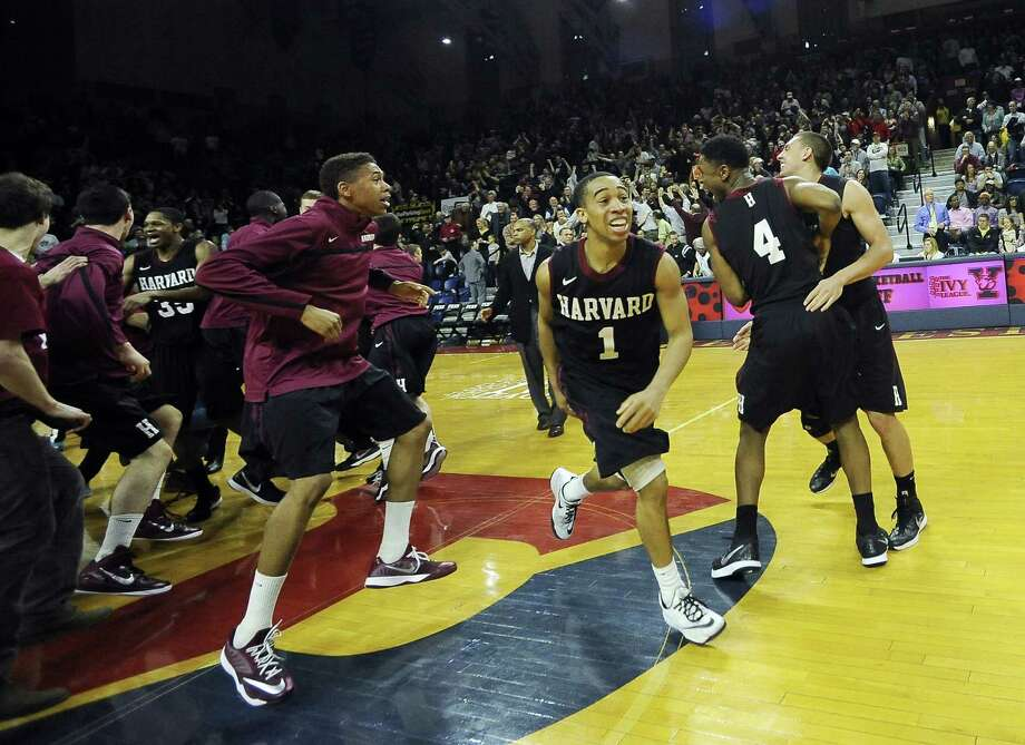 Harvard's Siyani Chambers (1) celebrates with his team after the Crimson beat Yale 53-51 in the Ivy League playoff on Saturday at The Palestra in Philadelphia. Photo: Michael Perez — The Associated Press  / FR168006 AP