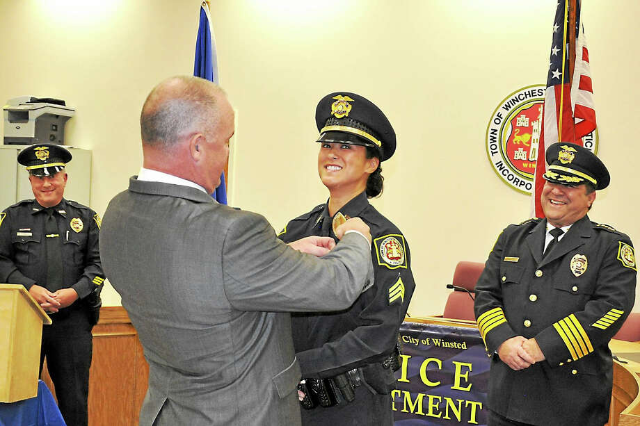 Winchester Police Chief William T. Fitzgerald Jr. proudly looks on as Sgt. Kim Boyne is pinned by her husband, New Milford Police Chief Shawn Boyne, during a ceremony in Winsted on Oct. 28. Photo: Photo By Lara S. Green-Kazlauskas
