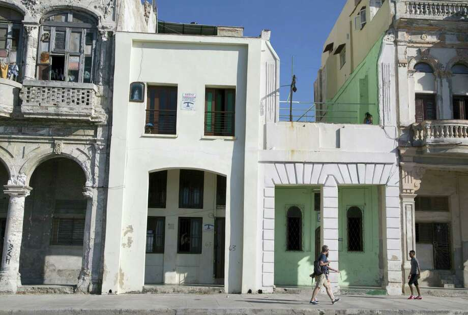 Tourists walk beside two privately owned houses with rooms for rent in Havana, Cuba on April 1, 2015. The wildly popular online home-sharing service Airbnb will allow American travelers to book lodging in Cuba. Photo: AP Photo/Desmond Boylan  / AP