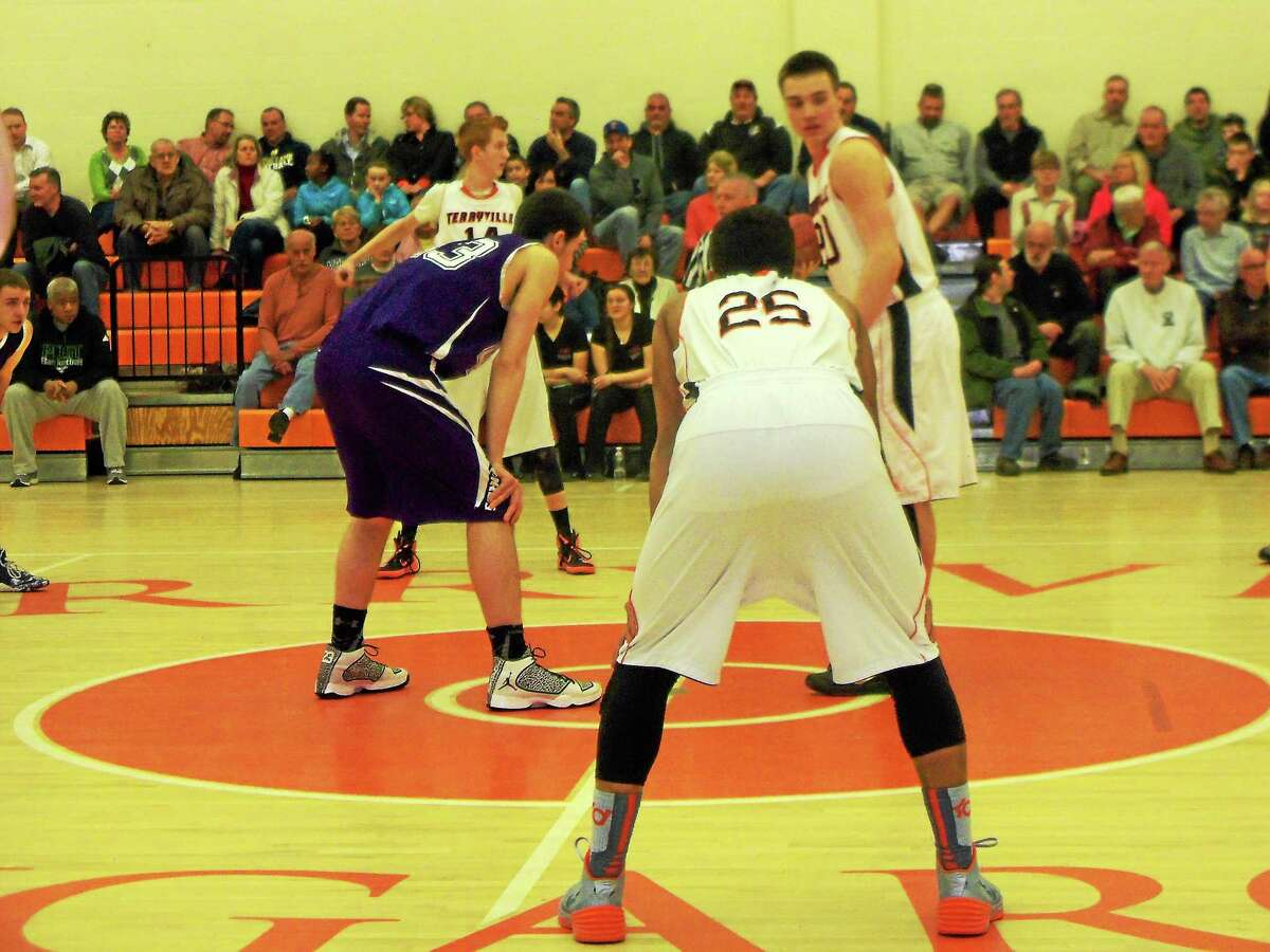 Peter Wallace - Register Citizen Terryville center Jeff Dupaul faces off with North Branford's Mark DiLauro while Kangaroos Ariel Batista (25) and Shea Tracy wait for the tap.