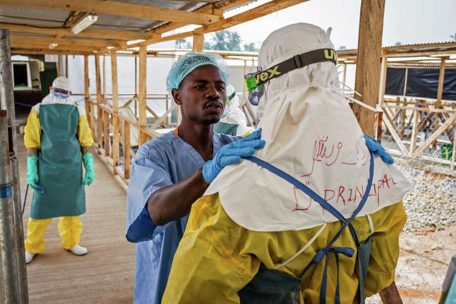 In this photo taken on Monday, March 2, 2015, a health care worker prepares a colleague's Ebola virus protective gear at an Ebola virus clinic operated by the International Medical Corps in Makeni, Sierra Leone. The World Health Organization says Thursday, March 12, 2015, its tally of Ebola deaths has passed the grim milestone of 10,000, mostly in West Africa.  (AP Photo/ Michael Duff) Photo: AP / AP