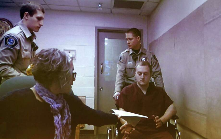 Adam Dees (right, in wheelchair) is pictured on a video screen during an arraignment at the Ada County Courthouse in Boise, Idaho Thursday March 12, 2015.  Bond was set at $2 million for Dees, based upon his possible involvement in the murders of Theodore, Delores and Thomas Welp. Dees is currently charged with three counts of grand theft, three counts of forgery and a single count of possessing a concealed weapon. (AP Photo/The Idaho Statesman, Kyle Green) Photo: AP / Idaho Statesman