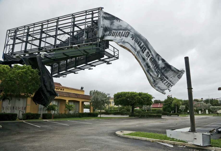 A billboard canvas flaps in the wind after Hurricane Matthew passed off shore, Friday, Oct. 7, 2016, in North Palm Beach, Fla.  Matthew was downgraded to a Category 3 hurricane overnight with the strongest winds of 120 mph just offshore as the storm pushed north, threatening hundreds of miles of coastline in Florida, Georgia and South Carolina. Photo: AP Photo/Wilfredo Lee   / Copyright 2016 The Associated Press. All rights reserved.