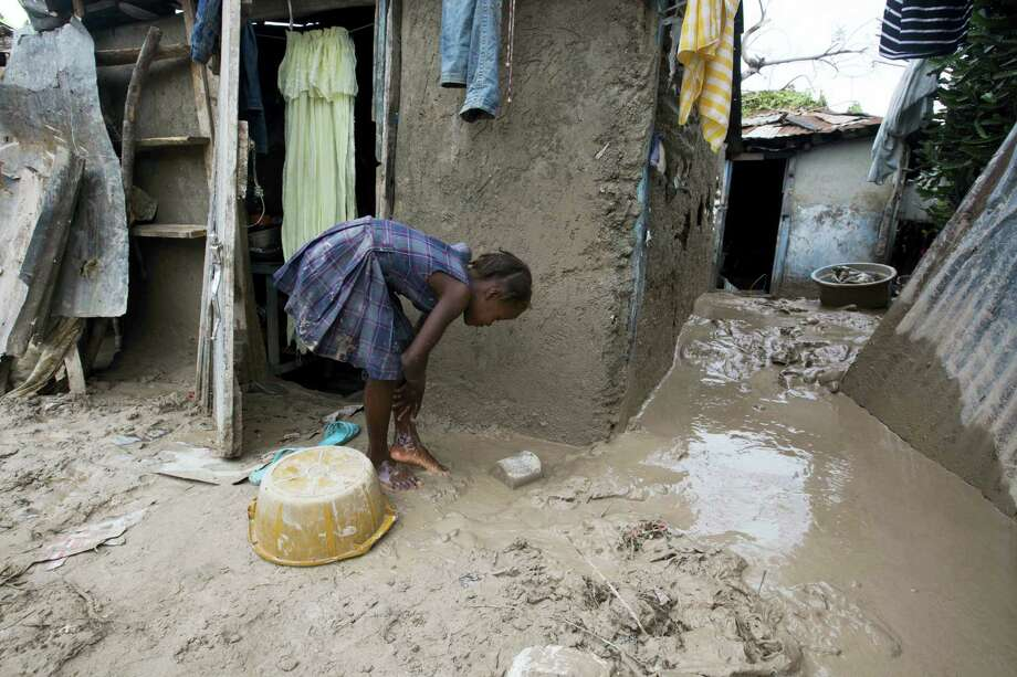 A girl washes mud from her feet after Hurricane Matthew passed in Les Cayes, Haiti, Thursday, Oct. 6, 2016. Two days after the storm rampaged across the country's remote southwestern peninsula, authorities and aid workers still lack a clear picture of what they fear is the country's biggest disaster in years. Photo: AP Photo/Dieu Nalio Chery   / Copyright 2016 The Associated Press. All rights reserved.