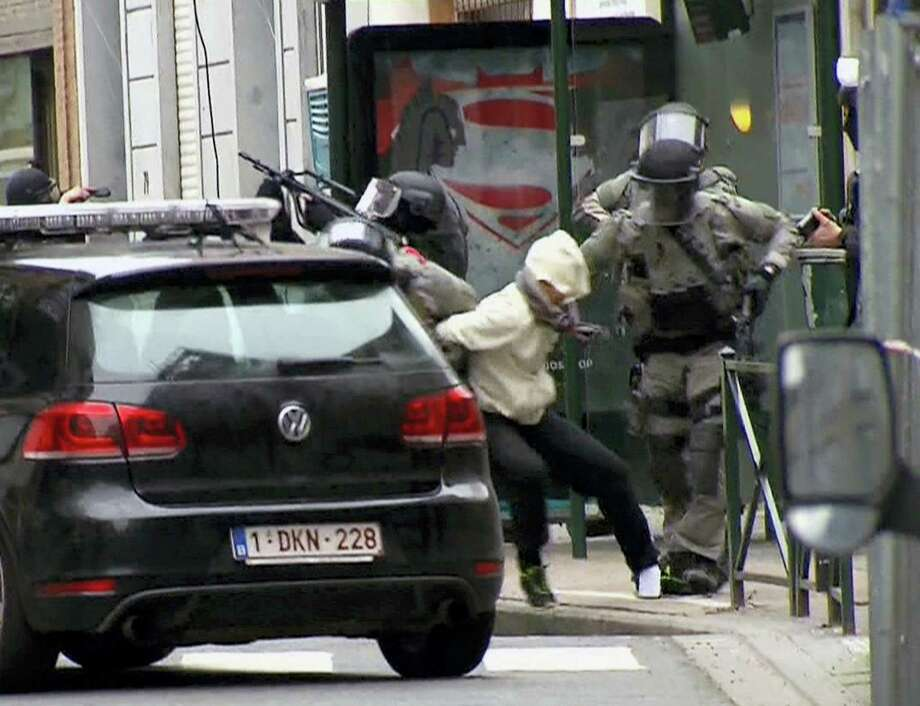 In this framegrab taken from VTM, something appears to drop from inside the trouser leg of Salah Abdeslam, centre, as he is arrested by police and bundled into a police vehicle during a raid in the Molenbeek neighborhood of Brussels, Belgium, Friday March 18, 2016.  After an intense four-month manhunt across Europe and beyond, police on Friday captured Salah Abdeslam, the top suspect in last year's deadly Paris attacks, in the same Brussels neighborhood where he grew up. Photo: VTM Via AP   / VTM