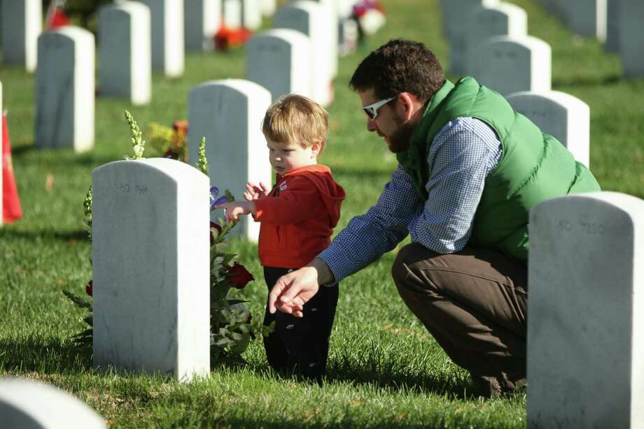 Army reservist Maj. Stephen Hedger of Washington, and his son, Lincoln, 1, visit the grave Wednesday, Nov. 11, 2015, of family friend Army Lt. Col. Dominic Rocco Baragon, who was killed in Iraq in 2003, at Section 60 of Arlington National Cemetery in Arlington, Va. Photo: AP Photo/Andrew Harnik   / AP
