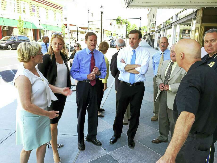 From left, Torrington Mayor Elinor Carbone, state Rep. Michelle Cook, and U.S. Sens. Richard Blumenthal and Chris Murphy, along with police and town officials, discuss the city's recently completed sidewalk replacement project on Main Street Wednesday morning. Photo: BEN LAMBERT — The Register Citizen