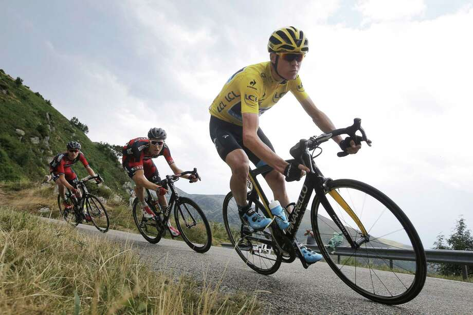 Chris Froome, wearing the overall leader's yellow jersey, is followed by Tejay van Garderen, far left, as they speed downhill during the twelfth stage of the Tour de France on Thursday. Photo: Laurent Cipriani — The Associated Press  / AP