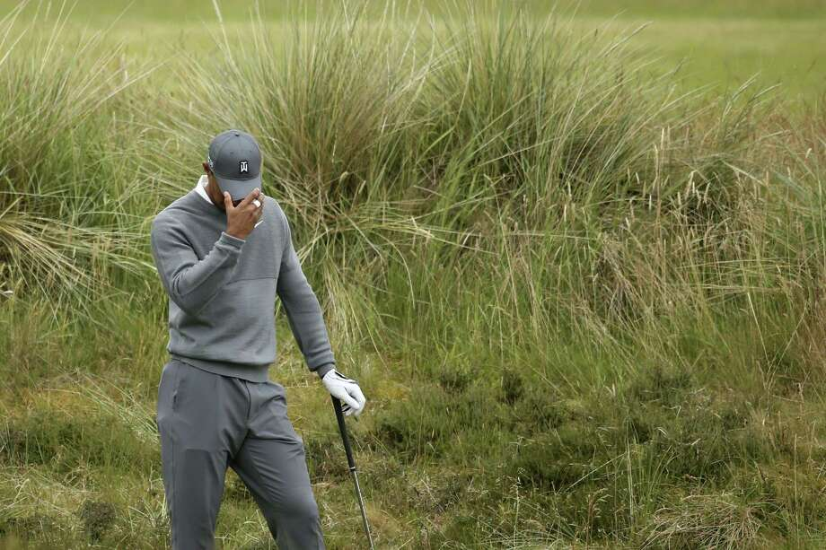 Tiger Woods prepares to take a shot from the rough on the fifth hole during the first round of the British Open on Thursday at the Old Course, St. Andrews, Scotland. Photo: Peter Morrison — The Associated Press  / AP