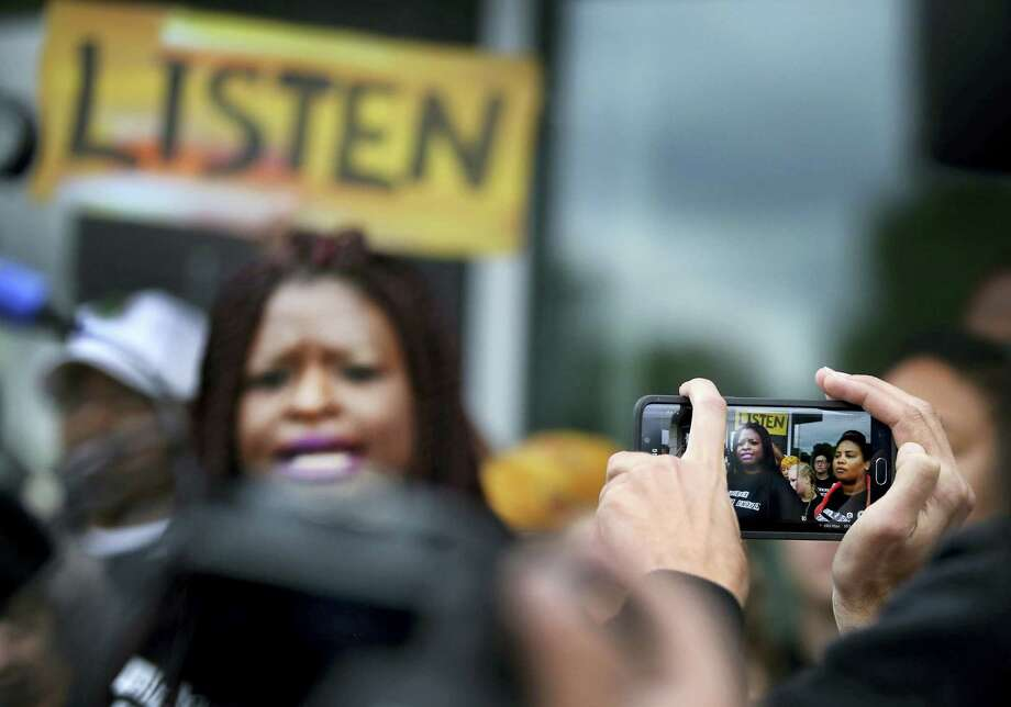 A member of the crowd takes a photo of Minneapolis NAACP President Nekima Levy-Pounds, center, as she speaks against police brutality during a press conference following U.S. Attorney Andrew Luger's announcement that no criminal civil rights charges will be filed against two white Minneapolis police officers in the November shooting death of Jamar Clark, Wednesday, June 1, 2016,  at the FBI local headquarters in Brooklyn Center, Minn. Photo: David Joles — Star Tribune Via AP / Star Tribune
