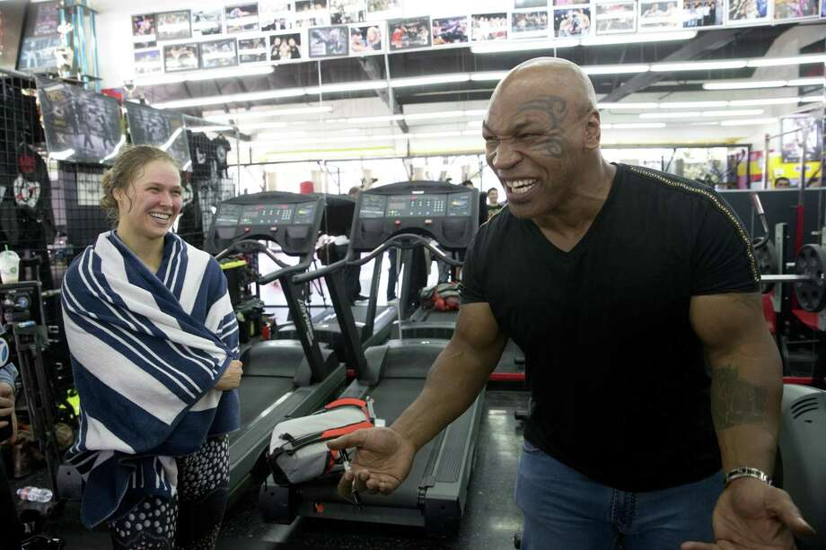 Mixed martial arts fighter Ronda Rousey, left, and former boxer Mike Tyson share a light moment after her workout Wednesday at Glendale Fighting Club in Glendale, Calif. Rousey, the UFC bantamweight champion, is scheduled to face Brazil's unbeaten Bethe Correia at UFC 190 in Rio de Janeiro on Aug. 1. Photo: Jae C. Hong — The Associated Press  / AP