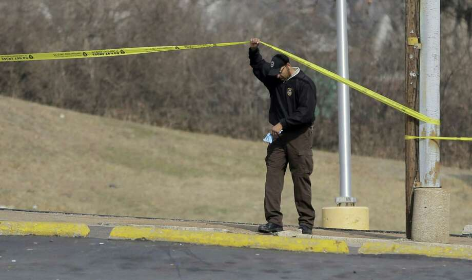 An investigator lifts crime scene tape near the Ferguson Police Department Thursday, March 12, 2015, in Ferguson, Mo. Two police officers were shot in front of the police department early Thursday as demonstrators gathered after the police chief resigned in the wake of a scathing Justice Department report alleging bias in the police force and local courts. Photo: (AP Photo/Jeff Roberson) / AP