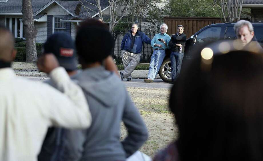Area residents look on as protesters march outside the family home of a former University of Oklahoma Sigma Alpha Epsilon fraternity member Parker Rice, Wednesday, March 11, 2015, in Dallas. Rice and several other fraternity members were seen on video chanting a racist song. (AP Photo/Brandon Wade) Photo: AP / FR168019 AP