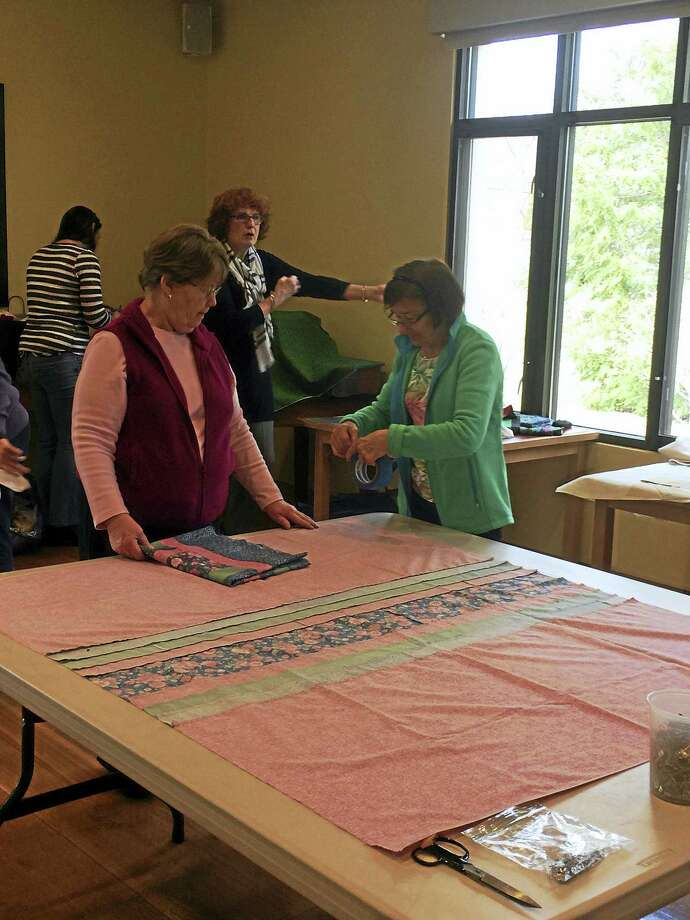 Noelia Ortiz - The Register CitizenQuilts That Care members prepare fabric for a new quilt, which will be donated to a patient at a local hospital, during their meeting at the Litchfield Community Center this week. Photo: Journal Register Co.