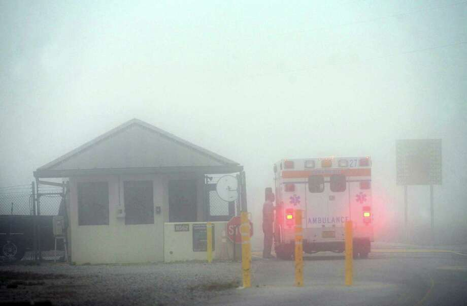 An Okaloosa County ambulance sits at the Eglin Air Force entrance in Fort Walton Beach, Fla., Wednesday, March 11, 2015.   Seven Marines and four soldiers aboard an Army helicopter that crashed over waters off Florida during a routine night training mission were presumed dead Wednesday, and crews found human remains despite heavy fog hampering search efforts, military officials said. Photo: (AP Photo/Northwest Daily News, Devon Ravine) / Northwest Daily News