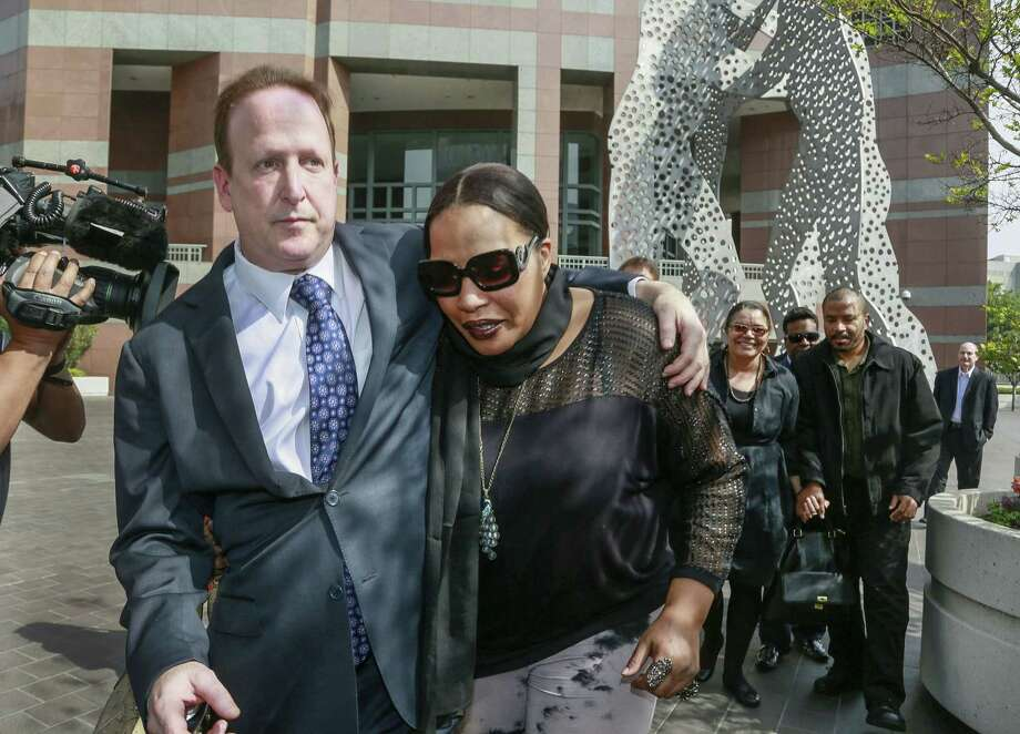 "Attorney Richard Busch, left, and Nona Gaye, daughter of the late Marvin Gaye, leave the Los Angeles U.S. District Court after a jury awarded the singer's children nearly $7.4 million after determining singers Robin Thicke and Pharrell Williams copied their father's music to create ""Blurred Lines,"" Tuesday, March 10, 2015. Gaye died in April 1984, leaving his children the copyrights to his music.  In the background, right, is Marvin Gaye's ex-wife, Jan Gaye, and son, Frankie Gaye. (AP Photo/Nick Ut) Photo: AP / AP"