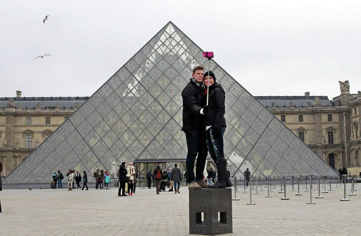 FILE - In this Tuesday, Jan. 6, 2015, Chris Baker and Jennifer Hinson from Nashville, Tennessee, use a selfie stick in front of the Louvre Pyramide in Paris. A French palace and a British museum have joined the growing list of global tourist attractions that have banned ìselfie sticksî _ devices visitors use to improve snapshots, but which critics say are obnoxious and potentially dangerous. Officials at Chateau de Versailles outside Paris and Britainís National Gallery in London announced the ban Wednesday, saying they need to protect both the artworks and other visitors. (AP Photo/Remy de la Mauviniere, File)