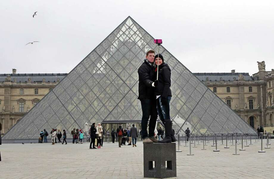 FILE - In this Tuesday, Jan. 6, 2015, Chris Baker and Jennifer Hinson from Nashville, Tennessee, use a selfie stick in front of the Louvre Pyramide in Paris. A French palace and a British museum have joined the growing list of global tourist attractions that have banned ìselfie sticksî _ devices visitors use to improve snapshots, but which critics say are obnoxious and potentially dangerous. Officials at Chateau de Versailles outside Paris and Britainís National Gallery in London announced the ban Wednesday, saying they need to protect both the artworks and other visitors. (AP Photo/Remy de la Mauviniere, File) Photo: AP / AP