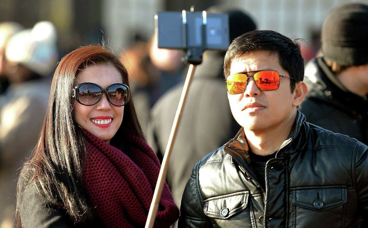 FILE - In this Jan. 23, 2015, file photo, tourists use a 'selfie stick' in London. A French palace and a British museum have joined the growing list of global tourist attractions that have banned ìselfie sticksî _ devices visitors use to improve snapshots, but which critics say are obnoxious and potentially dangerous. (AP Photo/PA, John Stillwell) UNITED KINGDOM OUT NO SALES NO ARCHIVE
