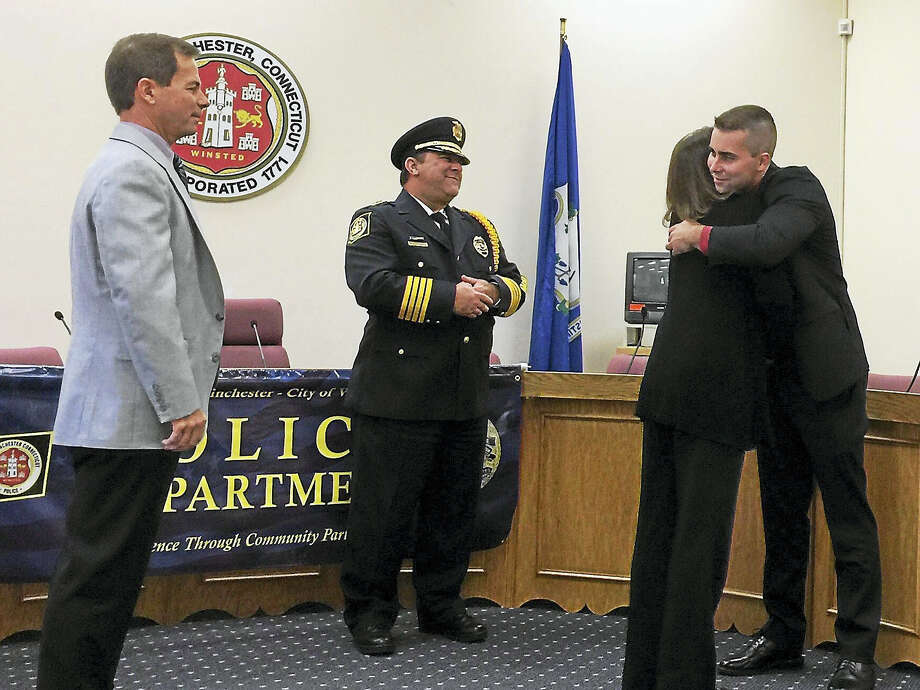 Nicholas C. Ryan, far right, gets a congratulatory hug from his mother, Deborah Ryan, after he was sworn in as a member of the Winchester Police Department Wednesday morning. Also  pictured is Police Chief William Fitzgerald, center, and Ryan's father, Edmond Ryan, left. Photo: Ben Lambert — The Register Citizen