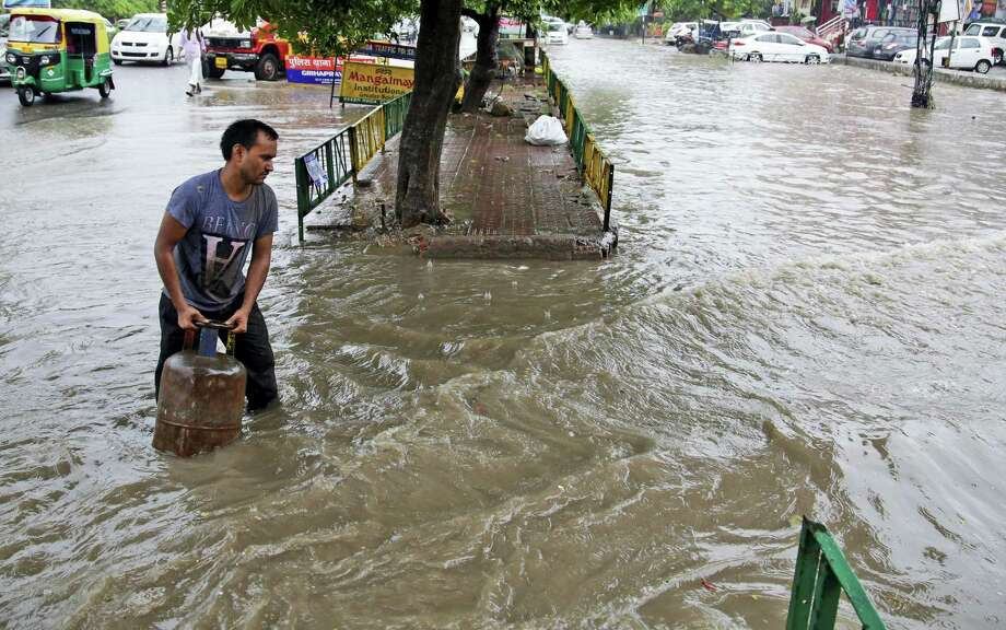 An Indian man carries a gas cylinder through a flooded street during a rainstorm in New Delhi, India, Saturday, July 30, 2016. Indian authorities are trying to rescue thousands of people stranded in flooded villages after a week of heavy rains killed at least 52 people and uprooted tens of thousands of others from their homes in Bihar state in the east and Assam in the northeast. Photo: AP Photo/Altaf Qadri   / Copyright 2016 The Associated Press. All rights reserved. This material may not be published, broadcast, rewritten or redistribu