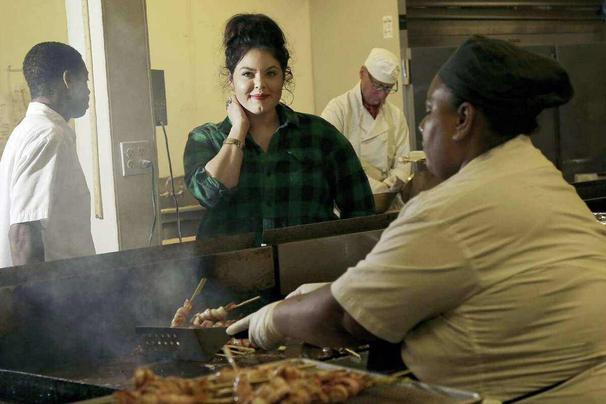 In this Sept. 28, 2016 photo, Olivia Colt, owner of catering company Salt & Honey, center, poses for photos as members of her cooking staff work in the kitchen in Berkeley, Calif. The campaign to give workers time off when they'are sick is picking up momentum.