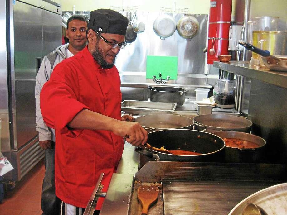 Monjur Ahmed prepares food in the kitchen. Photo: Photo By John Torsiello