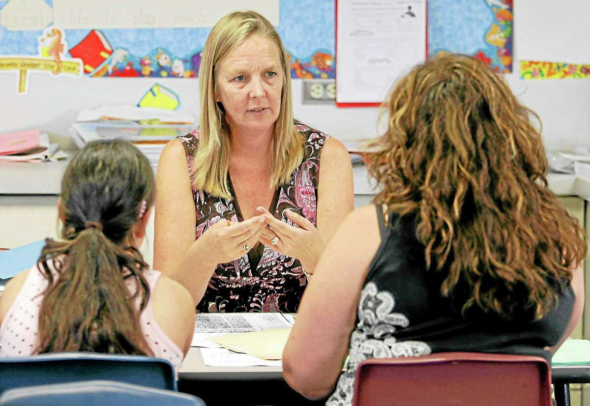 National Board Certified teacher Laurie Humphrey, center, talks with student Melinda Guzman, left, and her mother Yoli Guzman, right, at a parent-teacher conference in Chula Vista, Calif., in this file photo.
