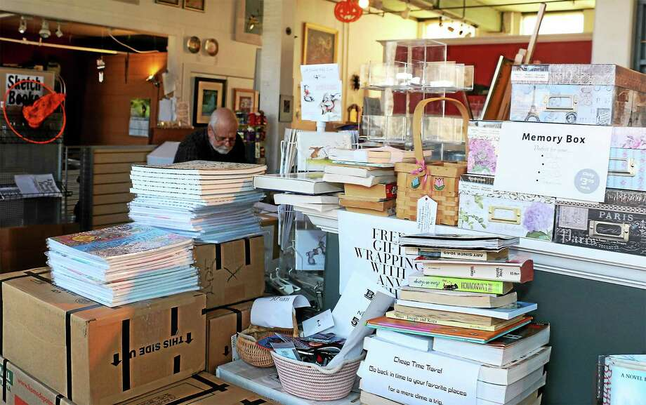 Many items have already been packed at Dickens Books and Art. In background is co-owner Bob Schwalb. Photo: John Fitts — The Register Citizen