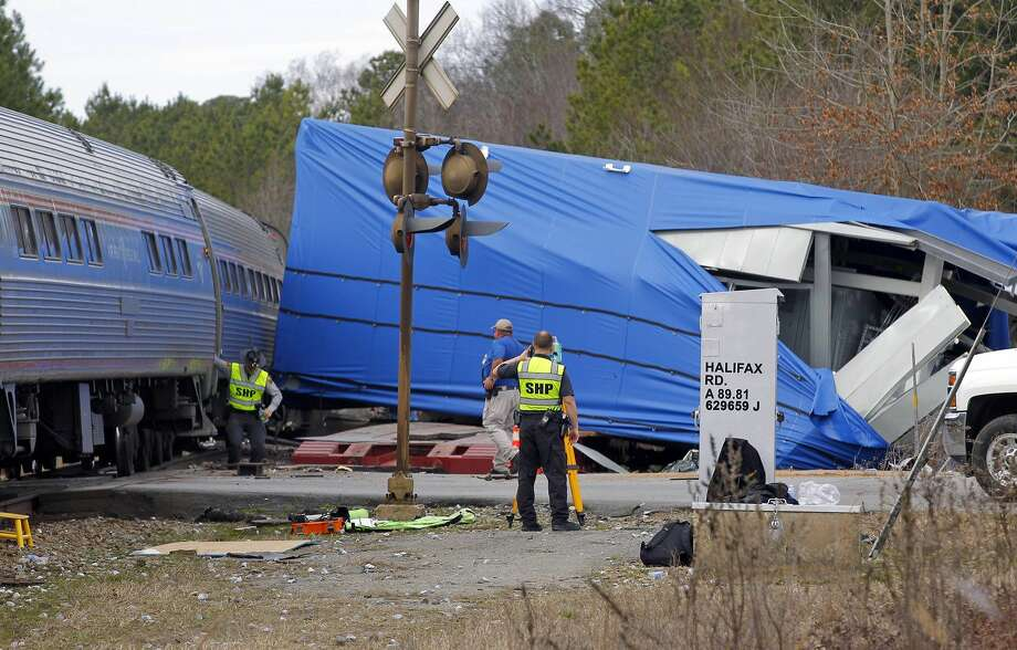 A northbound Amtrak train collided with an oversized truck carrying an electrical building when the truck got stuck on the tracks at the intersection of U.S. Hwy 301 and NC Hwy 903 in Halifax, NC on March 9, 2015.  Over 200 passengers were on the train bound for New York.  Some were injured but N.C. Highway Patrol spokesman Lt. Jeff Gordon said none of the injuries were life threatening.  The wreckage in the blue plastic wrap is the damaged electrical building that the truck was hauling.  (AP Photo/The News & Observer, Chris Seward) Photo: AP / The News and Observer