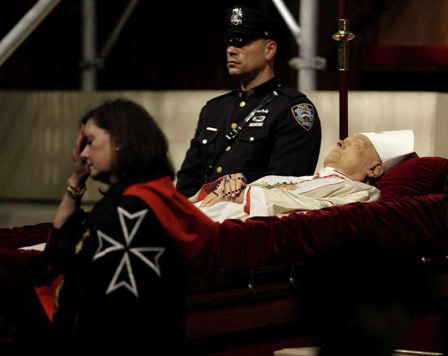 Officals stand around the body of Cardinal Edward Egan at a public viewing in St. Patrick's Cathedral in New York, Monday, March 9, 2015. Egan played a prominent role in New York City after the Sept. 11 terror attacks, and now New Yorkers are preparing to pay respects to the former archbishop after his death last week. (AP Photo/Seth Wenig) Photo: AP / AP