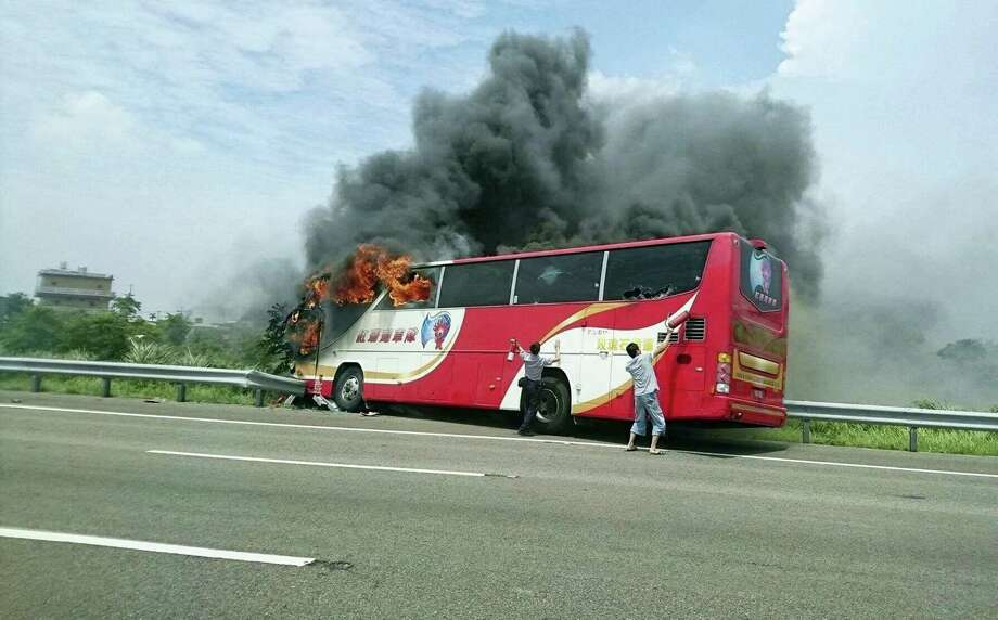 In this photo provided by Yan Cheng, a policeman and another man try to break the windows of a burning tour bus on the side of a highway in Taoyuan, Taiwan, Tuesday, July 19, 2016. Taiwanese investigators say the driver of the bus that crashed and burst into flames killing all 26 on board was driving drunk. Police coroners in Taoyuan county south of Taipei tested the driver's blood, urine and stomach contents and found all tested for alcohol concentrations above the legal limit. Photo: Yan Cheng/Scoop Commune Via AP   / Yan Cheng