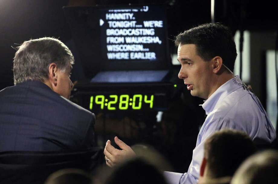 Wisconsin Gov. Scott Walker, right, gives a broadcast interview after announcing that he is running for the 2016 Republican presidential nomination at the Waukesha County Expo Center Monday in Waukesha, Wis. Photo: AP Photo  / AP