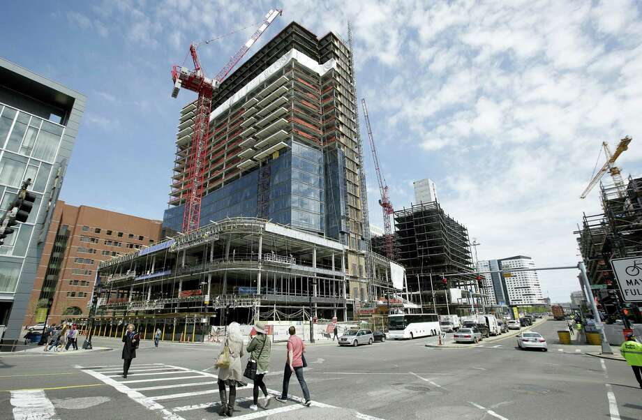 In this Thursday, May 19, 2016, file photo, passersby walk near the construction site of a high-rise building in Boston. On Friday, July 29, 2016, the Commerce Department issued the first estimate of how the U.S. economy performed in the April-June quarter. It was generally disappointing. Photo: AP Photo/Steven Senne   / Copyright 2016 The Associated Press. All rights reserved. This material may not be published, broadcast, rewritten or redistribu