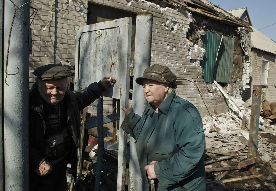 """An elderly couple stand in front of their badly damaged house in Debaltseve, Ukraine, Monday, March 9, 2015. More than 6,000 people have died in eastern Ukraine since the start of the conflict almost a year ago that has led to a """"merciless devastation of civilian lives and infrastructure,"""" according to the U.N. human rights office. (AP Photo/Vadim Ghirda) Photo: AP / AP"""