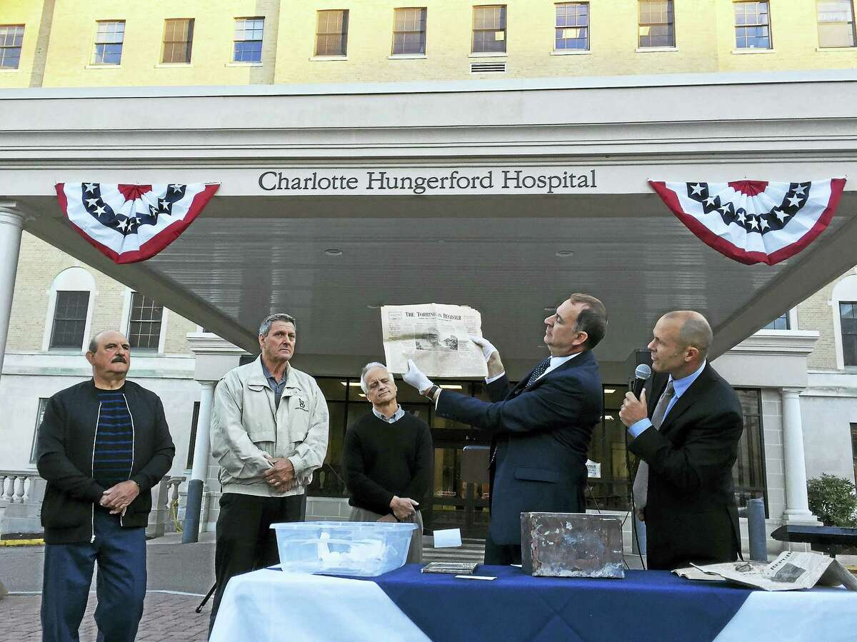 Ben Lambert - The Register Citizen The community marked the 100th anniversary of Charlotte Hungerford Hospital Wednesday evening, as a commemorative ceremony was held on the hospital grounds in Torrington. Above, Tim LeBouthillier, center, director of Community Relations & Development, with Brian Mattiello, vice president of Organizational Development, holds a vintage copy of the Torrington Register that chronicled the hospital's growth.