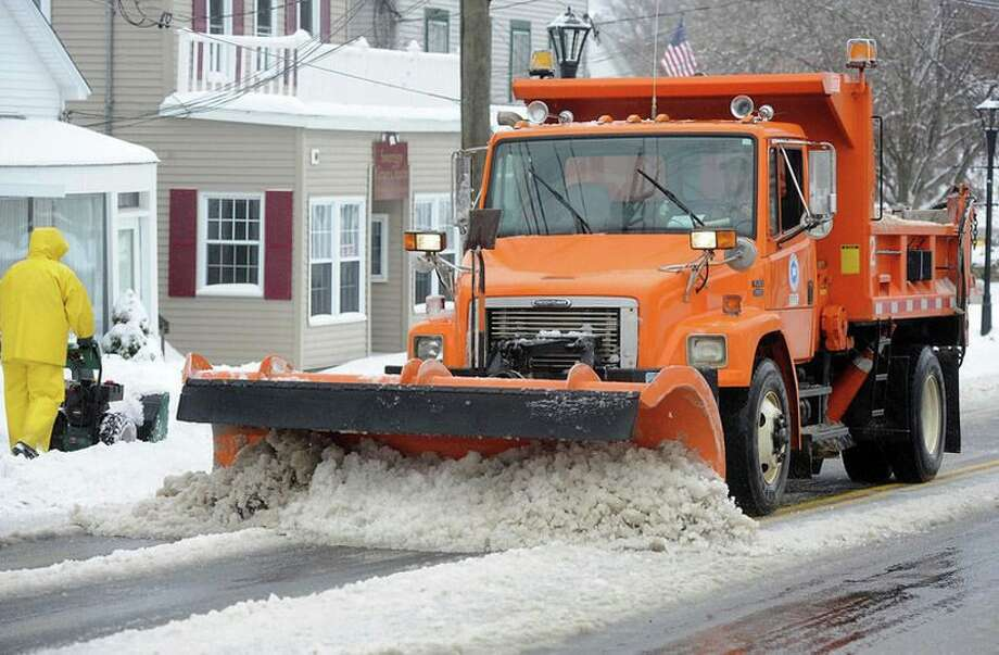 A plow truck clears snow off the road. Photo: File Photo
