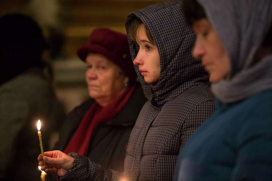 People take part in a memorial religious service for plane crash victims at the St.Isaac's Cathedral in St.Petersburg, Russia on Nov. 8, 2015. Mourners have packed into the landmark St. Isaac's Cathedral in St. Petersburg for a memorial service for victims of the Russian plane crash, and as a choir sang, the bell of the world's fourth-largest cathedral was tolling once for each of the 224 victims. Photo: AP Photo/Elena Ignatyeva  / AP