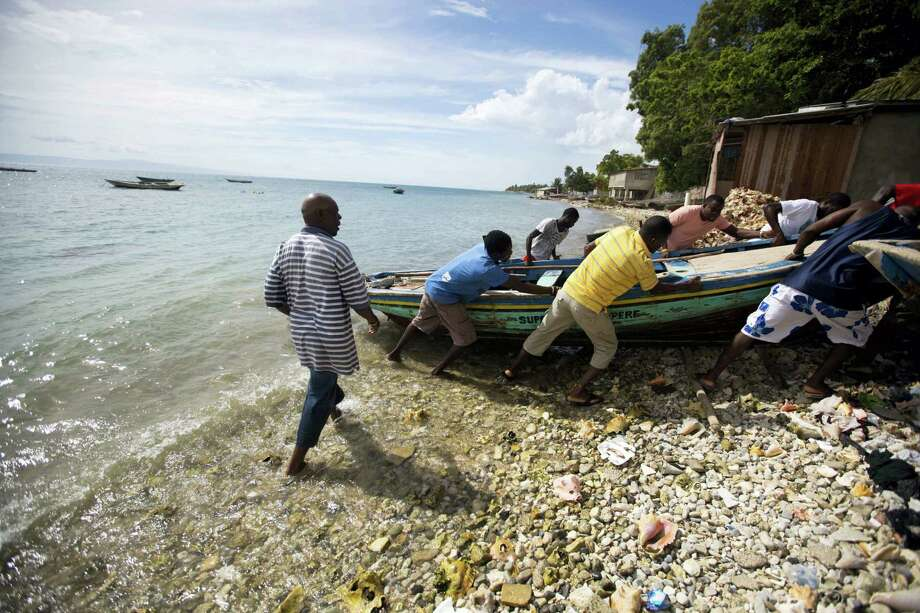 Fishermen move their boats out of the water before the arrival of Hurricane Matthew in Arcahaie, Haiti. Sunday Oct. 2, 2016. A powerful Hurricane Matthew moved slowly Sunday across the Caribbean Sea on a track that authorities warned could trigger devastation in parts of Haiti. Photo: AP Photo/Dieu Nalio Chery   / Copyright 2016 The Associated Press. All rights reserved.