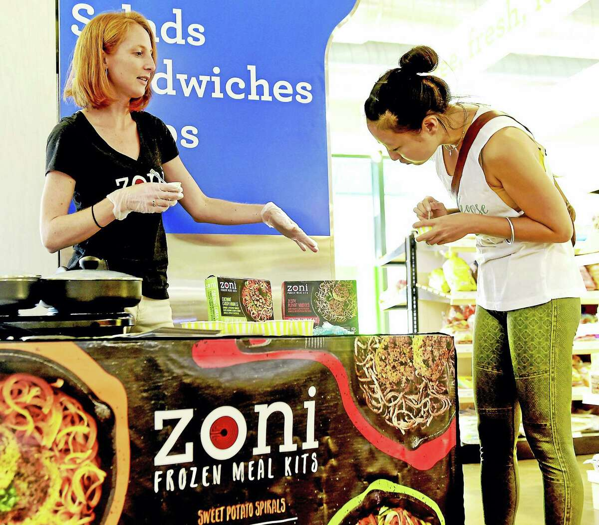Zoe Lloyd, left, a Yale University graduate and co-founder of Zoni Frozen Meal Kits, shows off the plant-based frozen foods to Julia Zhao of Hamden during a food tasting demonstration at Elm City Market in New Haven recently.