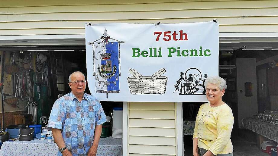Jerry Belli and wife Gaye Belli, both 70, stand in front of a banner for the Belli family reunion, which was held at their home on Mountain Road in Torrington Saturday. Photo: Photo By N.F. Ambery